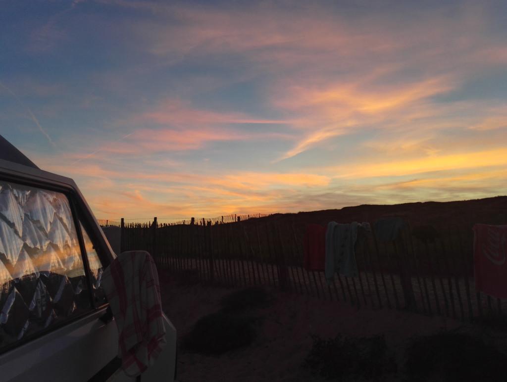 VW T3 mit Blick auf Strand und Sonnenuntergang