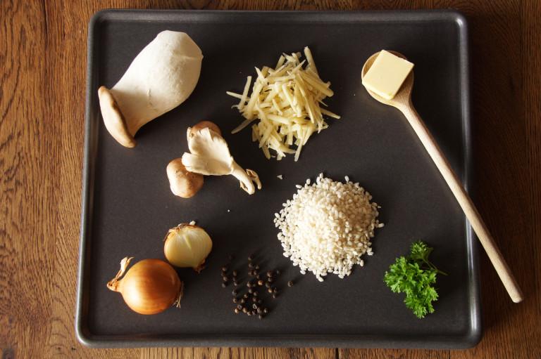 Kräuterseidlinge, Austernpilze und andere Zutaten auf Holztisch