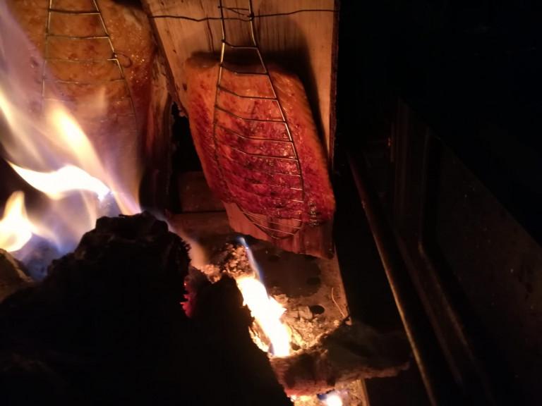 Flammlachs auf Birkenbrett vor Feuer Abends