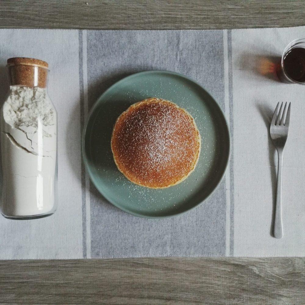 Pancakes neben Pancakes mit Ahornsirup und Puderzucker