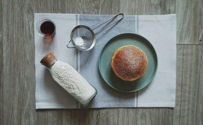 Pfannkuchen auf Teller mit Puderzucker. Daneben Ahornsirup und Pancake-Mix