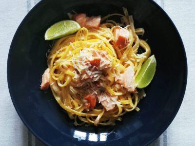 Pasta mit Lachs, Parmesan auf blauem Teller