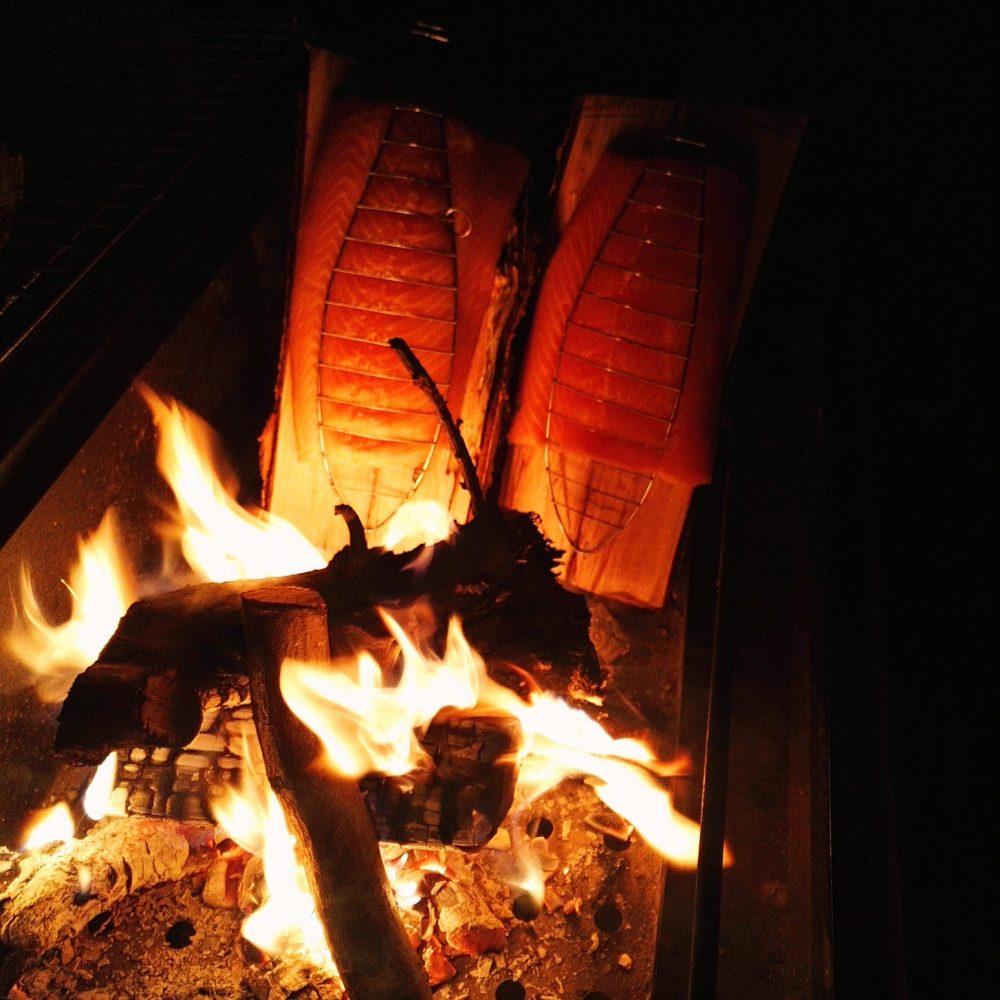 Flammlachs vor Holzfeuer und Flammen