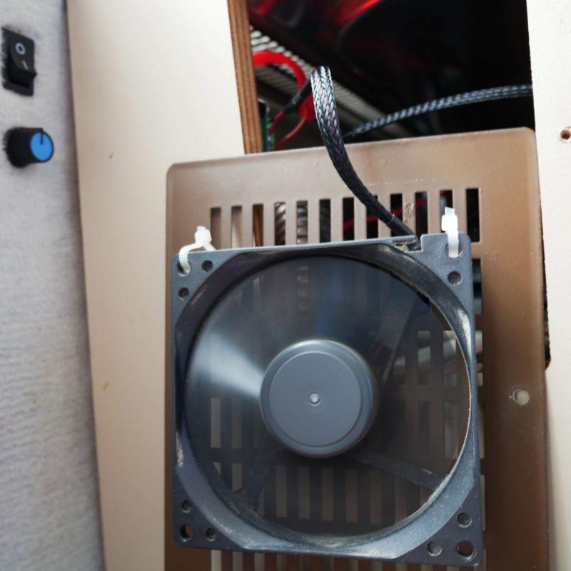 PC-Lüfter dreht sich mit hoher Drehzahl und ist an einem Kühlgitter im VW T3 mit Kabelbindern befestigt